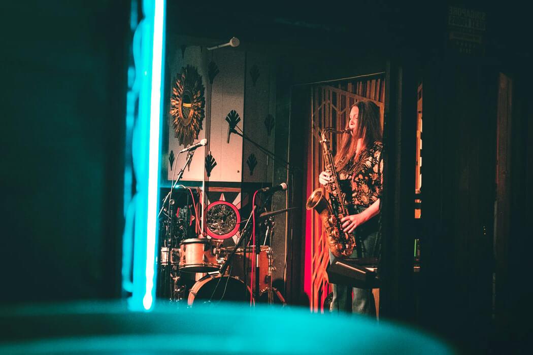 Девушка играющая на саксофоне в заведении